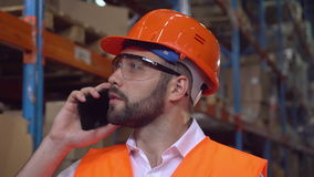 Closeup employee in storage. Portrait manager at work in warehouse. Handsome worker talking by smartphone discussing the logistics . Man with beard wearing hard