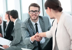 Closeup of the employee welcomes colleague with a handshake befo Stock Images