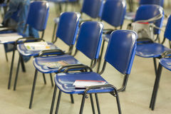 Closeup of Empty Chairs in Line with Workbooks Laid Upon It. Stock Image