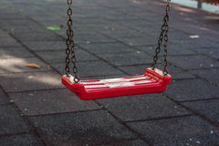Closeup of an empty red chain swing Royalty Free Stock Images