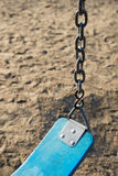 Closeup of an empty swing in kids playground. Vertical Stock Photography