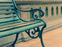 Closeup empty vintage bench in front of rugged wall Stock Image