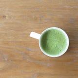 Closeup en kopp av varmt grönt te på den rena trätabellen i morni Fotografering för Bildbyråer