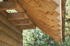 Closeup of the end of rafters on log house roof construction. Closeup of the end of rafters on roof construction of log house from spruce with moss stock images