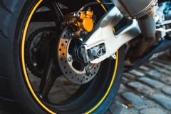 Closeup enduro metal shiny steel  brake pads of Fast extreme motorbike Motorcycle bike speed baggy, rimes with yellow sport stripe. Wheels and disk  fast royalty free stock images