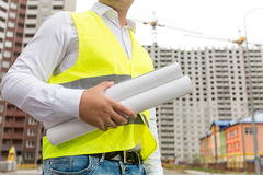 Closeup of engineer holding rolled blueprints in background of b. Closeup photo of engineer holding rolled blueprints in background of building site Stock Image