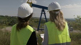 Closeup of engineers supervisors women with helmet examining oil pump platform rig extracting activity with tablet -. Closeup of engineers supervisors women with stock video footage