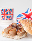 Closeup of English sausage sandwich with, brown sauce, cup of te Royalty Free Stock Photos