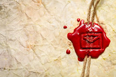 Closeup of envelope symbol imprinted in red sealing wax. On old wooden table stock photography