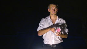Closeup European Conjurer Shows Card Tricks. Closeup young european conjurer in white shirt shows tricks with cards in black background stock video