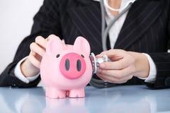 Closeup on examining piggy bank. Royalty Free Stock Photos