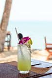 Closeup of an exotic cocktail on a table at beach Royalty Free Stock Photo