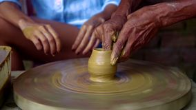 Experienced potter makes clay pot on wheel lady watches. Closeup experienced old master makes clay pot on rotating potter wheel lady watches in pottery workshop stock footage