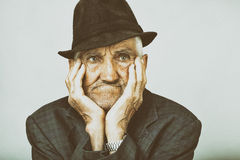 Closeup of expressive old man holding face in hands Royalty Free Stock Photography
