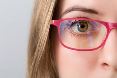 Closeup of and eye of blonde woman with pink glasses Royalty Free Stock Images