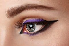 Closeup eye with makeup - arrow black and lilac Stock Photo