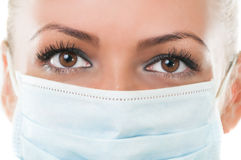 Closeup of the eyes of dentist assistant wearing mask Stock Photos