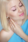 Closeup eyes makeup. Blond girl model touching her neck. Stock Image