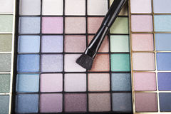 Closeup of eyeshadow cosmetics. Closeup shot of eyeshadow cosmetics with eyeshadow brush royalty free stock photo