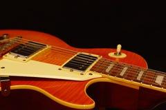 Closeup för gitarr för jazz för honungsunbursttappning elektrisk på svart bakgrund grunt djupfält Arkivbilder