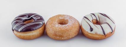 Closeup för olika sorter av vita choklader och bruna donuts Fotografering för Bildbyråer
