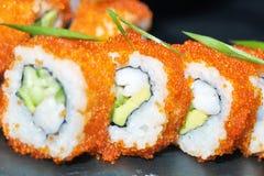 Closeup för sushirullar Japansk mat i restaurang Uppsättning för Kalifornien sushirulle med den lax-, ål-, grönsak- och för flygf arkivfoto