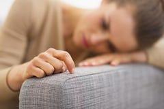 Closeup förestående av frustrerat ungt hemmafrusammanträde på soffan arkivbild