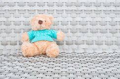 Closeup a fabric bear doll sit on wood weave chair texture background with copy space Royalty Free Stock Photography