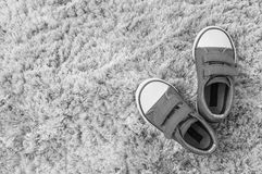 Closeup fabric sneakers of kid on gray carpet textured background in top view in black and white tone with copy space. Closeup fabric sneakers of kid on gray Royalty Free Stock Images