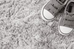 Closeup fabric sneakers of kid on gray carpet textured background in top view in black and white tone with copy space. Closeup fabric sneakers of kid on gray Stock Photos