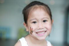 Closeup face of Asian child girl with butterfly tattoo sticker on cheek.  stock photo