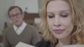Closeup face of beautiful blond woman reading aloud the book in the foreground while modestly dressed man looking at the. Close-up face of a beautiful blond stock video footage