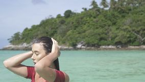 Beautiful girl on paradise beach. Closeup face of beautiful brunette woman in red bikini making her hair wet and walking in the sea water of paradise island stock video footage
