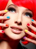 Closeup face of a beautiful  girl with  multicolor nails. Royalty Free Stock Photography