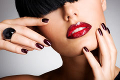 Closeup face of a woman with beautiful sexy red lips and dark na Stock Photography