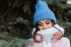 Closeup face of a young Smiling woman enjoying winter wearing knitted scarf and hat. royalty free stock photos
