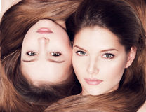 Closeup faces of mother and little daughter 8 years with long. Portrait of the beautiful faces of mother and little daughter 8 years with long hair royalty free stock photography