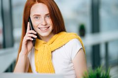 Closeup facial portrait of happy redhead woman on mobile phone call royalty free stock photo