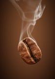 Closeup falling coffee bean with smoke on brown background. Falling coffee bean with smoke on brown background Royalty Free Stock Photos