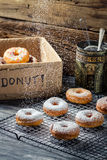 Closeup of falling icing sugar on fresh donuts Stock Images