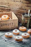 Closeup of falling icing sugar on fresh donuts Stock Image