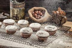 Closeup of falling powder sugar on chocolate muffins Royalty Free Stock Photography