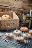 Closeup of falling powder sugar on fresh donuts. On old wooden table Royalty Free Stock Image
