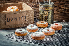Closeup of falling powder sugar on fresh donuts. On old wooden table Stock Photo