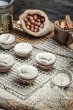 Closeup of falling powder sugar on fresh vanilla muffins Royalty Free Stock Photo