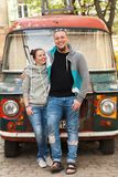 Closeup of family couple near colorful paintyng old car or gypsy hippie van. royalty free stock photography