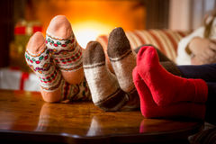 Closeup of family feet in wool socks at fireplace Stock Photo