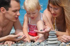 Closeup family on sea coast and pyramid of stones Stock Images