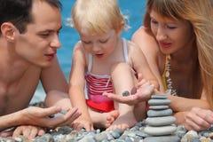 Closeup family on sea coast and pyramid of stones Stock Images