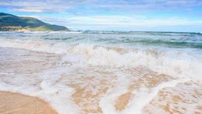 Closeup Fantastic Wave Surf on Golden Sand Beach Blue Sky Hill. Closeup panorama of fantastic wave surf on golden sand beach against blue sky and hill stock video